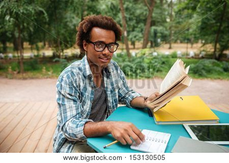 Happy attractive african young man studying outdoors