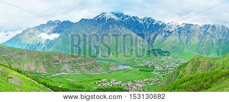The picturesque green valley with the colorful houses of Stepantsminda (Kazbegi) and winding Terek River with the snowy mountains on the background Georgia.