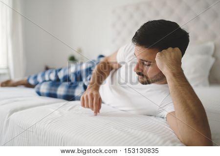 Heartbroken lonely man in pajamas on bed