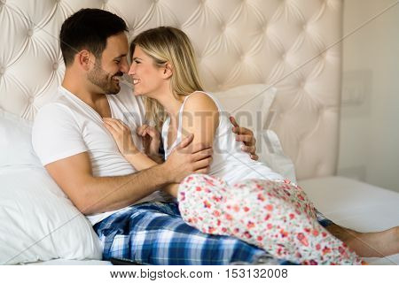 Happy young married couple smiling in bed