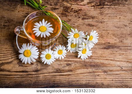 Cup of herbal tea with chamomile flowers on wooden table
