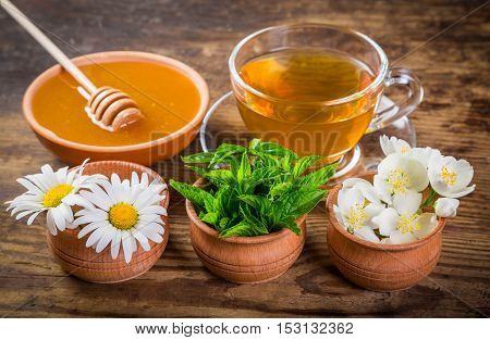 Herbal tea with mint, chamomile, jasmine flowers and honey on old rustic wooden table