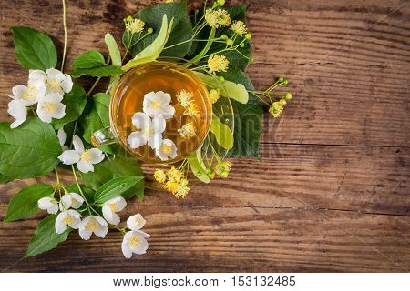 Herbal tea with jasmine and linden flowers on rustic wooden table, above view, space for text