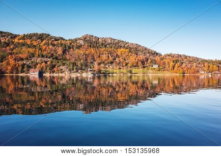 Coastal forest with reflection in still water. Norwegian landscape. Snillfjord Sor-Trondelag Vingvagen fishing camp