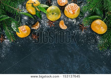 Top framework of mandarins with  evergreen twigs and star anise over spotty black surface