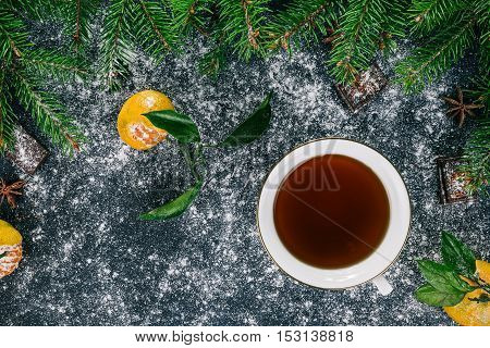 Cup of tea over black surface covered with sugar powder and decorated with frame of evergreen twigs, tangerines, chocolate and star anise