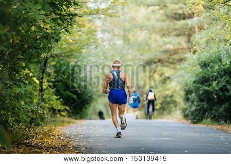 sports elderly man athlete running in autumn forest marathon