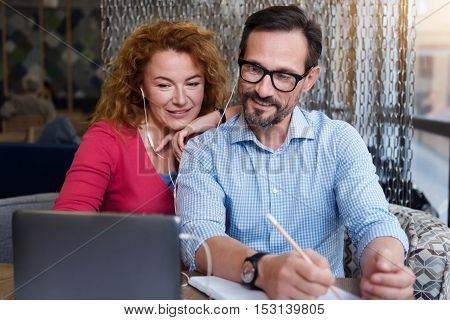 Getting tasks. Pretty ginger woman leaning on her male partner taking notes while getting information from tablet through earphones.
