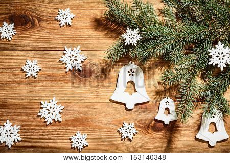 Christmas wooden background with white wooden snowflakes and coniferous branch.
