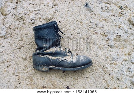 worn leather military boots on the sand
