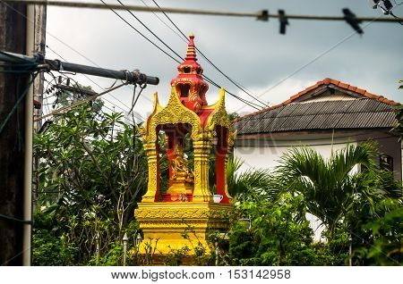 small golden buddhistic sprit house in tropical nature
