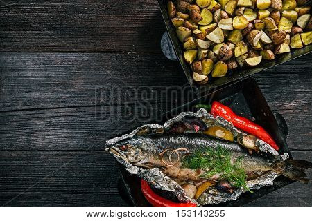 Whole salmon fish baked on tray in foil and chopped potatoes baked on the same tray. Flat lay