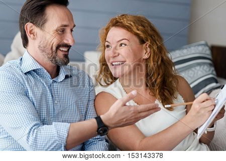 Here it is. Bearded man pointing at notes of ginger woman holding them while smiling.