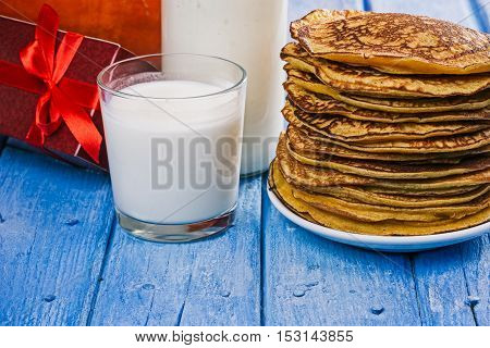 Stack of prepared pumpkin pancakes with milk and red gift box