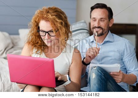 Tied up. Beautiful red-haired woman wearing glasses using her new laptop while bearded man behind taking notes.
