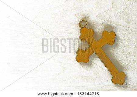 Ancient golden cross on white wooden background