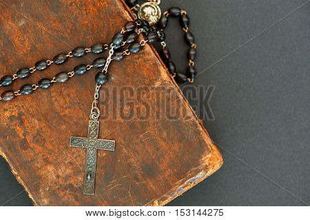 Old silver cross with black beads on an ancient book (Holy Bible)