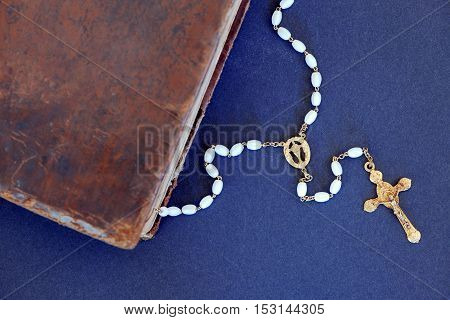 Corner of old book (Holy Bible) and a golden cross necklace with white beads
