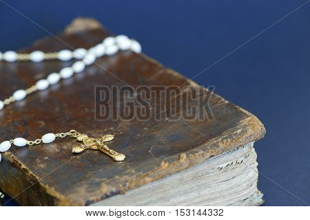 Closeup of an old golden cross and an ancient Bible against blue background
