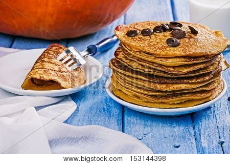 Stack of prepared pumpkin pancakes with chocolate drops