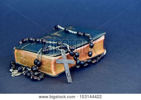 Ancient Holy Bible with an old silver cross necklace against blue background