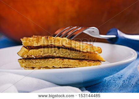 Piece of pumpkin pancakes stack on the plate near big orange pumpkin