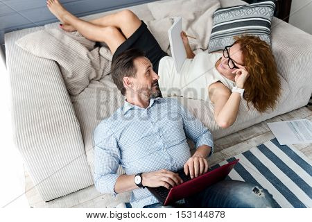 Common activity. Top view of barded man using laptop while leaning on couch where ginger woman holding notebook with pencil.