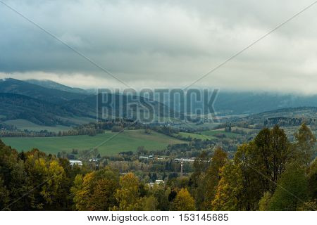 Seasonal landscape with morning fog in valley. Clouds drenched valley below the level of the mountains. Sunrise over creeping clouds