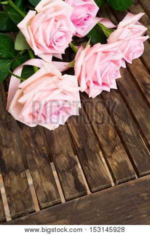 Heap of pink fres blooming roses on wooden table with copy space