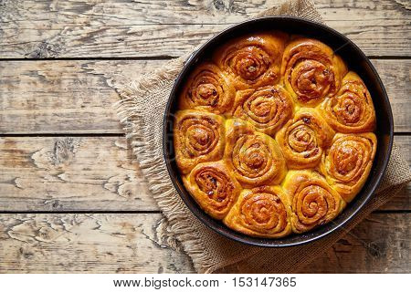 Pumpkin cinnamon bun rolls homemade sweet fall dessert bread food on vintage wooden table background