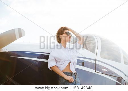 Beautiful young woman in sunglasses standing outdoors near small private aircraft