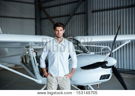 Confident attractive young man standing in front of small aircraft