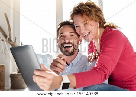 Happy together. Cheerful middle-aged couple holding laptop and laughing against window.