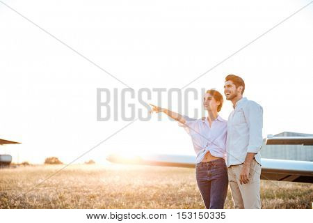 Young happy couple together during sunset standing at the field