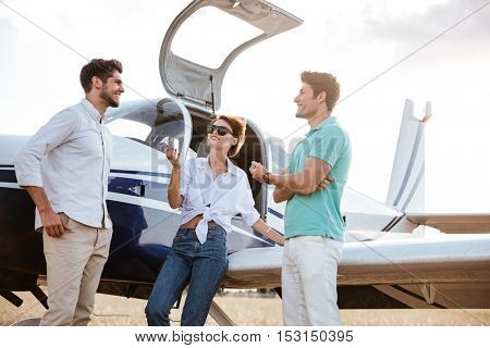 Three happy young friends standing and talking near small plane