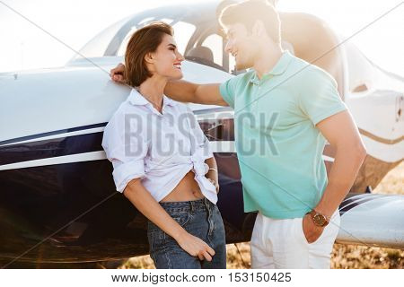 Happy young couple talking and flirting near private airplane