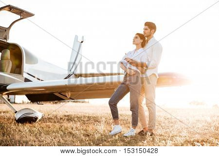 Happy couple on a honeymoon standing at the airplane field at sunset