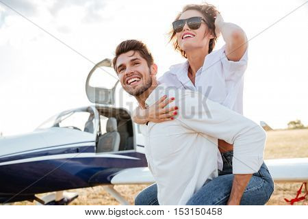 Happy young couple laughing and having fun on runway near private aircraft