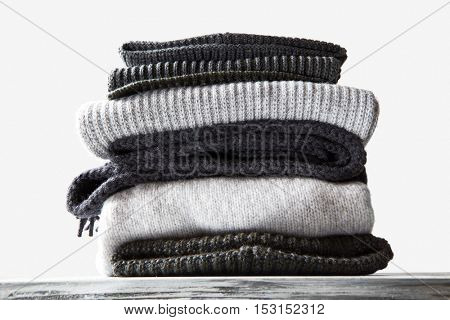 stacked black and grey knitted sweaters