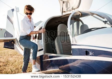Beautiful young woman pilot going to fly in small airplane