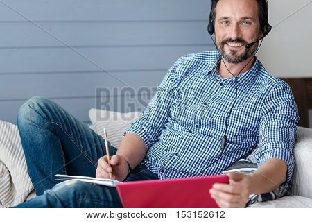 Work in comfort. Handsome bearded man wearing headphones with microphone holding laptop and notebook while sitting on couch.