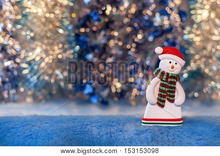 Figurine of a snowman on colorful background bokeh. New Year or Christmas picture.