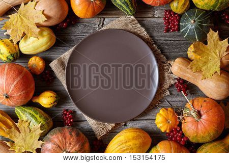 Autumn pumpkin harvest decoration frame empty blank space for design text with plate Thanksgiving dinner or Halloween setting on vintage wooden background wallpapper
