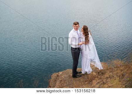 young beautiful couple bride and groom at a wedding walk by the lake.