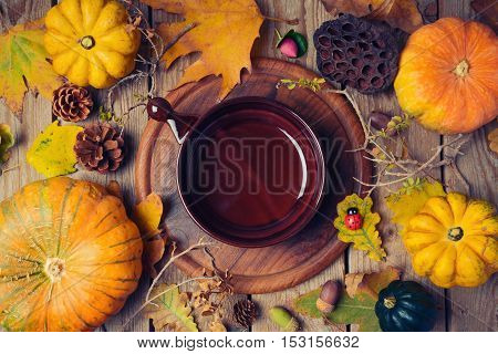 Thanksgiving dinner background with plate. Autumn pumpkin and fall leaves on wooden table. View from above