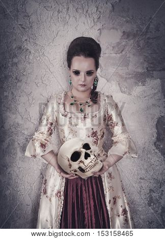 Beautiful witch woman in medieval dress holding human skull in hands