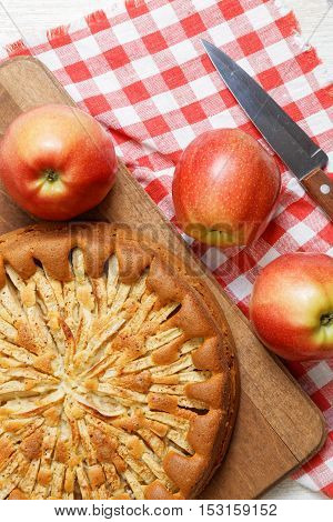 Homemade apple pie topped with slices of apples and cinnamon on wooden cutting board. Nearby are red apples knife and checkered napkin. Top view.