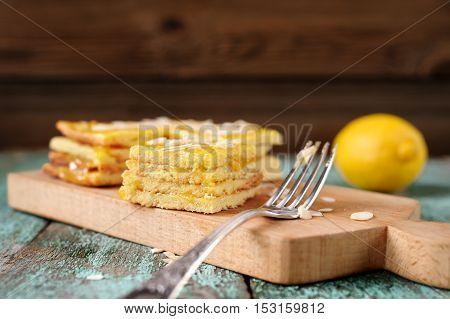 Homemade tasty layered lemon cake and whole lemon closeup