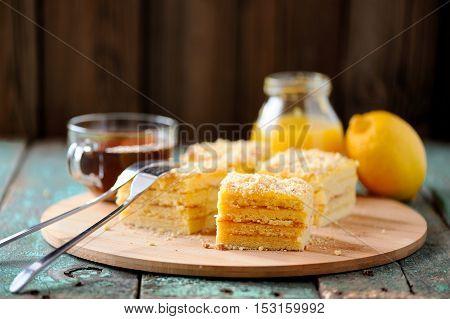 Homemade yummy layered lemon cake served with tea and lemon curd on bamboo plate selective focus