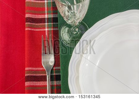 Table setting with two white plates fork wineglass over colorful napkins. Top view. Horizontal.